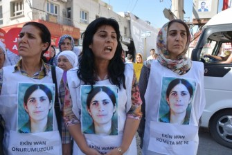 Kurdish protesters hold placards with Ekin Wan's face on August 19.