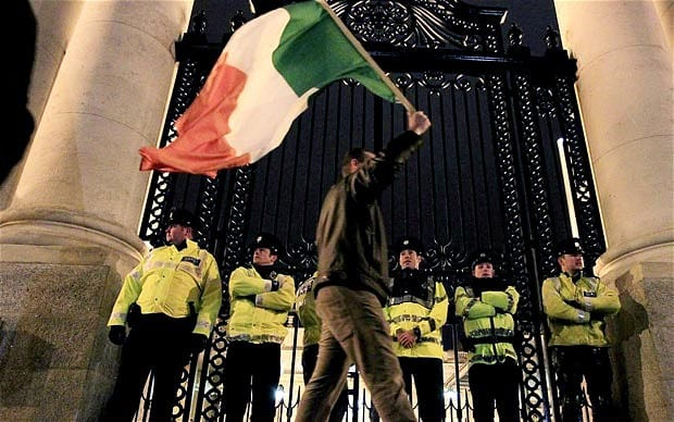 A protester waves the tricolour at a protest against the Troika bailout of Ireland in 2010