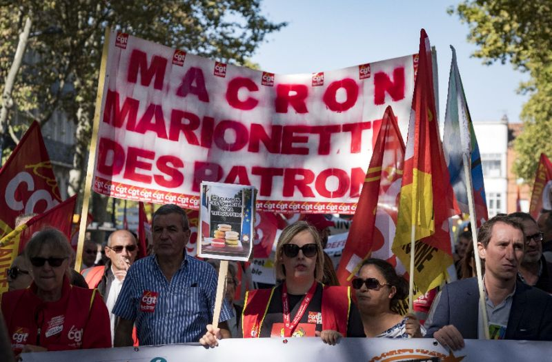 "Trade unionists rally against French President Emmanuel Macron's attacks on labour rights with a banner saying ""Macron, puppet of the employers"" (AFP)"